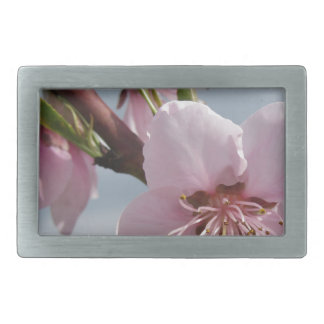 Blossoming peach tree against the cloudy sky rectangular belt buckle