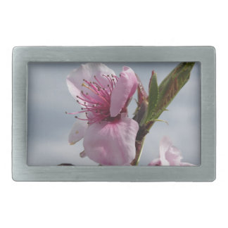 Blossoming peach tree against the cloudy sky rectangular belt buckles