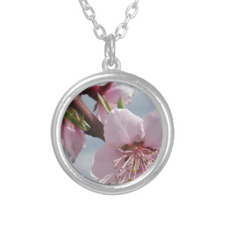 Blossoming peach tree against the cloudy sky silver plated necklace