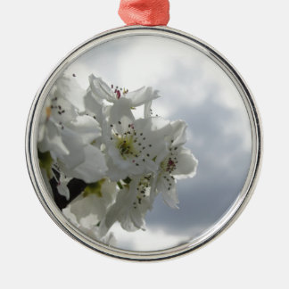 Blossoming pear tree against the cloudy sky metal ornament