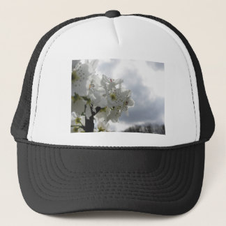 Blossoming pear tree against the cloudy sky trucker hat
