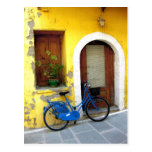 Blue bicycle against a yellow wall postcard