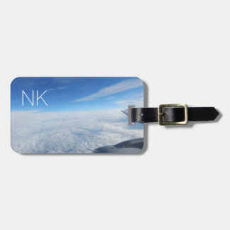 blue cloudy sky with monogram luggage tag