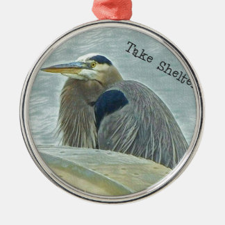blue heron sheltering from wind behind boat on lak metal ornament