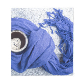 Blue scarf tied around the mug with hot coffee notepad