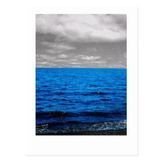 Blue sea, black and white sky postcard.