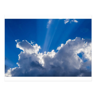 Blue sky with white clouds and ray of sunshine. postcard