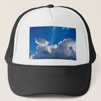 Blue sky with white clouds and ray of sunshine. trucker hat