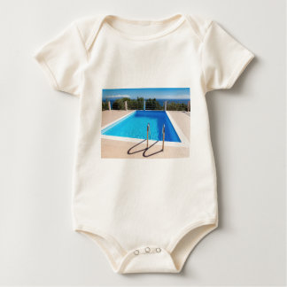 Blue swimming pool with steps at sea baby bodysuit