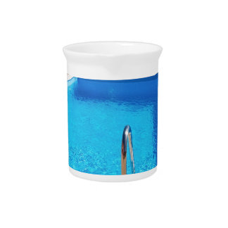 Blue swimming pool with steps at sea beverage pitchers