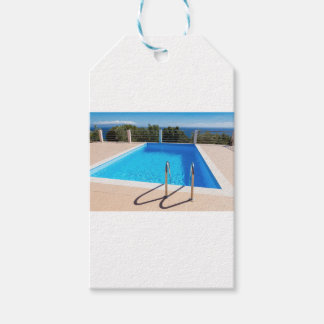 Blue swimming pool with steps at sea gift tags