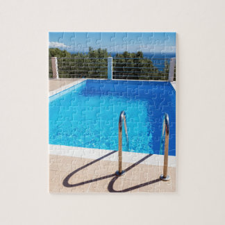 Blue swimming pool with steps at sea jigsaw puzzle