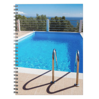 Blue swimming pool with steps at sea notebook