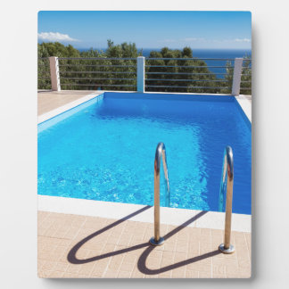 Blue swimming pool with steps at sea plaque