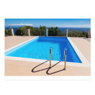 Blue swimming pool with steps at sea postcard
