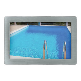 Blue swimming pool with steps at sea rectangular belt buckles