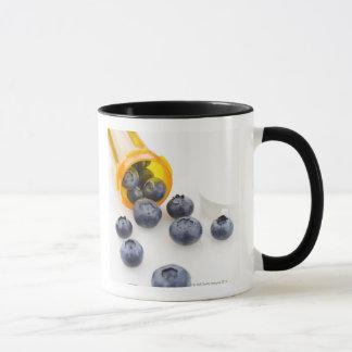 Blueberries spilling from prescription bottle mug