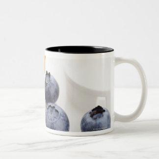 Blueberries spilling from prescription bottle coffee mugs