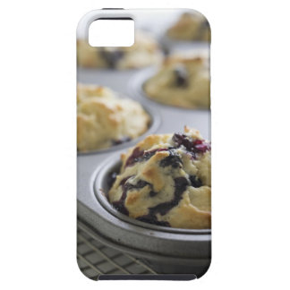 Blueberry muffins in a baking tin on a cooling iPhone 5 covers