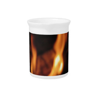 Blurred flames in a burning fireplace on black pitcher