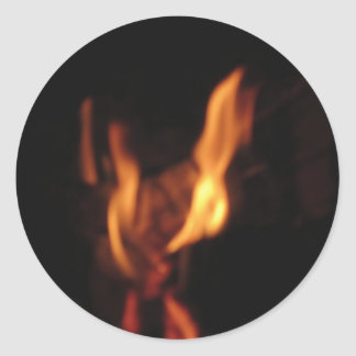 Blurred flames in a burning fireplace on black round sticker