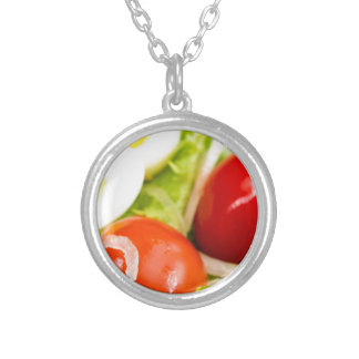 Blurred image of cherry tomatoes in a salad silver plated necklace