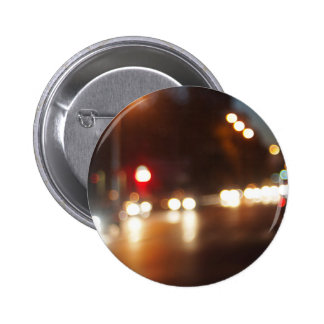 Blurred out of focus lights from cars in a night s 6 cm round badge