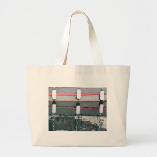 Boat fenders hanging on the board large tote bag
