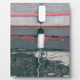 Boat fenders hanging on the board plaque