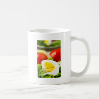 Boiled egg on a plate with lettuce, onions coffee mug