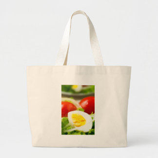 Boiled egg on a plate with lettuce, onions large tote bag