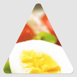 Boiled egg on a plate with lettuce, onions triangle sticker