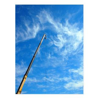 Boom of the crane on a diagonal against a blue sky postcard