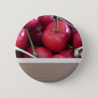Border of fresh cherries on wooden background 6 cm round badge