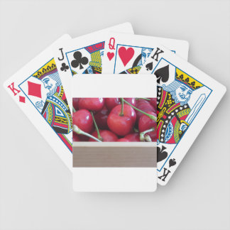 Border of fresh cherries on wooden background bicycle playing cards