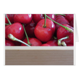 Border of fresh cherries on wooden background card