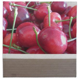 Border of fresh cherries on wooden background napkin