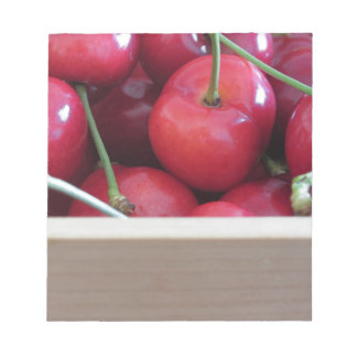 Border of fresh cherries on wooden background notepad