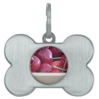 Border of fresh cherries on wooden background pet tag