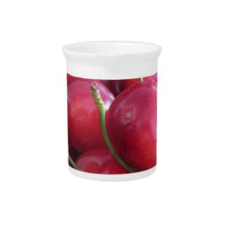 Border of fresh cherries on wooden background pitcher