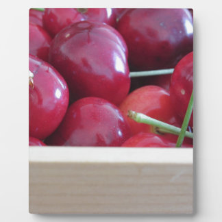 Border of fresh cherries on wooden background plaque