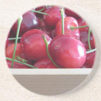 Border of fresh cherries on wooden background sandstone coaster