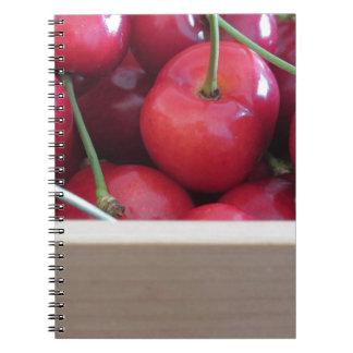 Border of fresh cherries on wooden background spiral note book