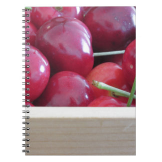 Border of fresh cherries on wooden background spiral notebooks