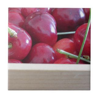 Border of fresh cherries on wooden background tile