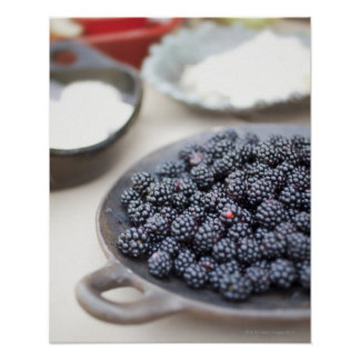 Bowl of blackberries on a table poster