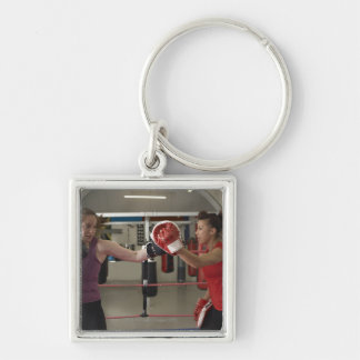 Boxer training with coach in gym key chains