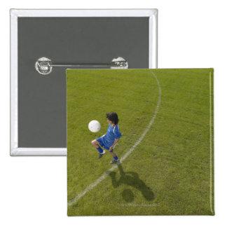 Boy (8-10) footballer practicing skills, 15 cm square badge