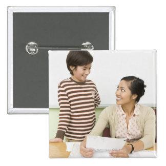 Boy and teacher at teachers desk 15 cm square badge