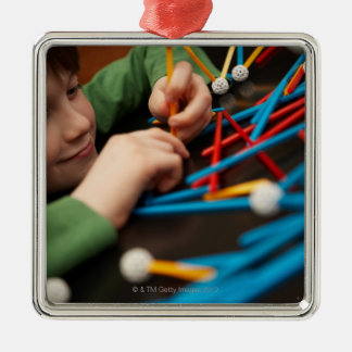 Boy connecting molecules for science project metal ornament